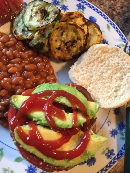 Veggie burger with tomato and avocado, baked beans, and grilled zucchini